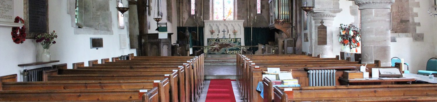 The aisle in Upton Bishop church with a red carpet and the altar
