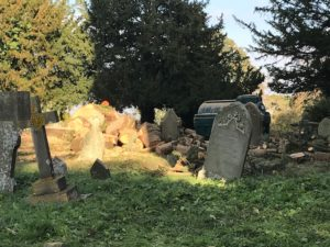 Gravestones and cut logs in the churchyard