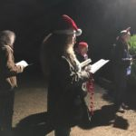 A group of carol singers in the dark