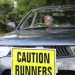 car with caution runners sign