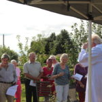 Vicar in white talking to a group of people