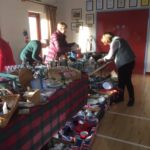 People looking at bric a brac on a table