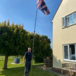 Smiling man with golden retriever standing by a flagpole with a union jack flg