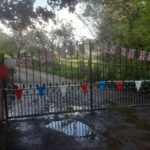 Union jack flags, bunting and balloons on a metal gate