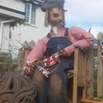 Scarecrow wearing denim dungarees and a pink hat and carring union jack bunting