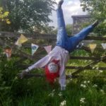 Scarecrow with red hair, wearing jeans and hanging upside down on a wooden gate