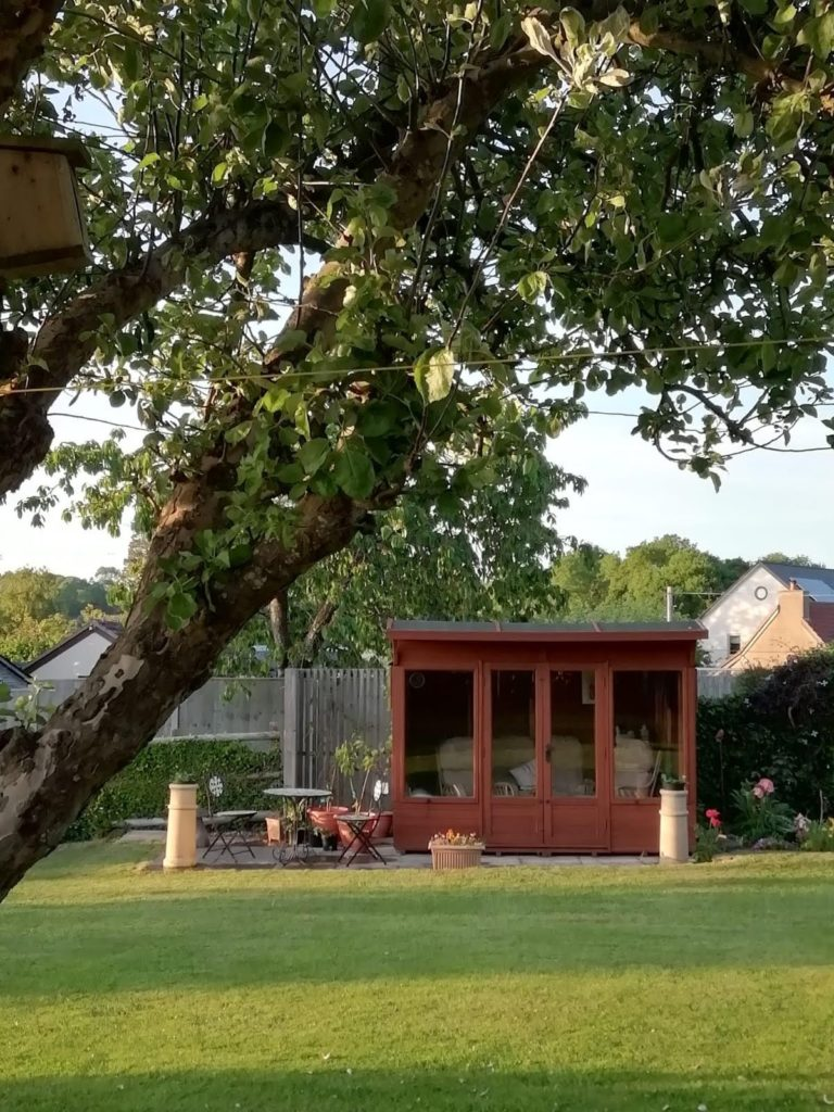 A garden with a summerhouse and a tree