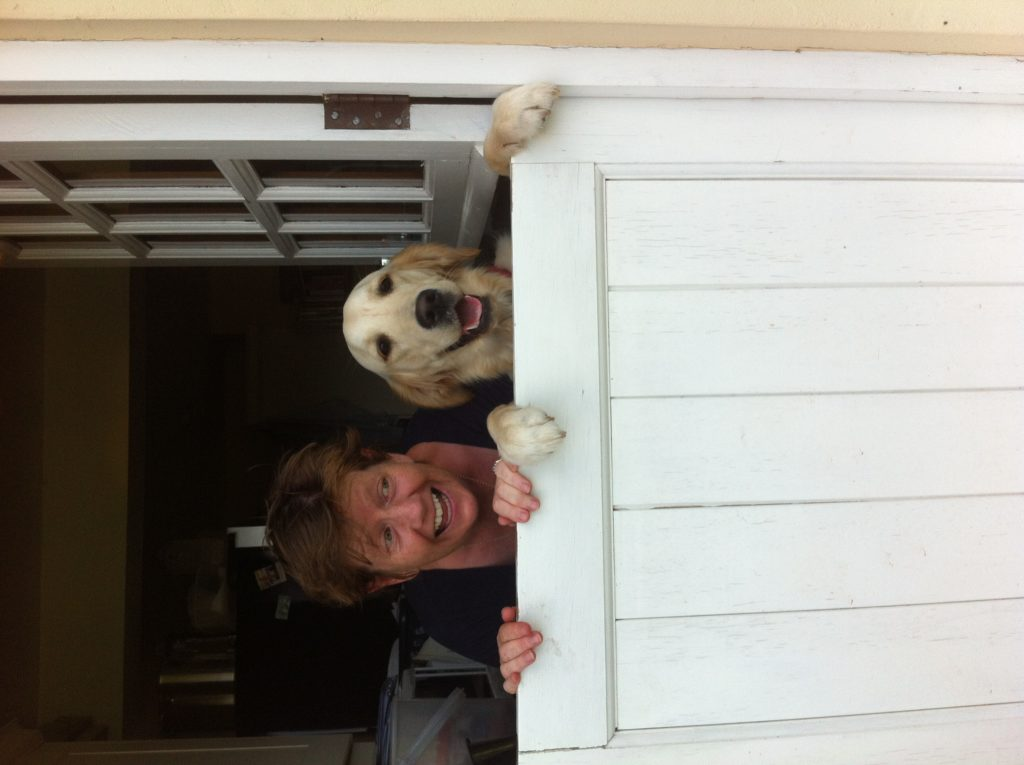 A woman and a dog looking out over a stable door