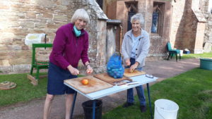 Two women cutting up apples outside the church
