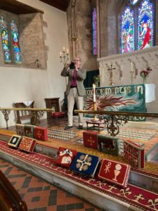 The Bishop of Hereford taking a photo on his mobile phone in front of the altar