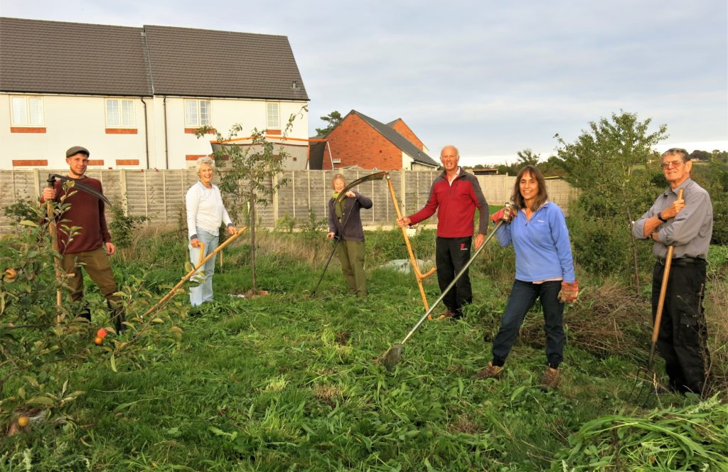 The village scything team with their tools at the community orchard