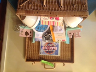 Wicker hamper with baking accessories and a cook book