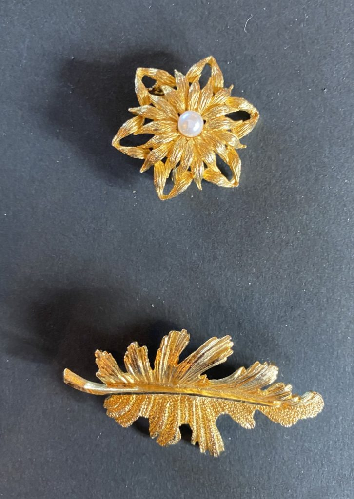 gold coloured flower brooch and a gold coloured leaf brooch
