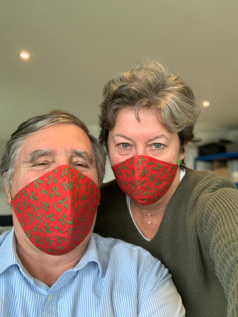 A man and a woman modelling the Christmas face masks