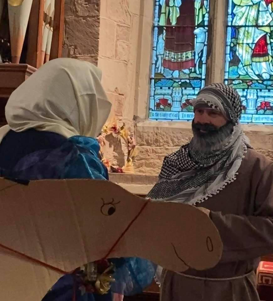 A woman dressed as Mary and a man dressed as Joseph talking with a cardboard camel
